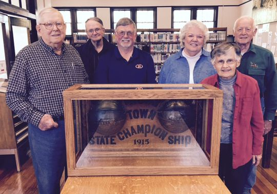 Cliff Woody (from left), Gordon Wait, David White, Martha Randel, Florence Emma Peery and Cliff Beesley surround the trophy for the 1915 Indiana state basketball champions of Thorntown High School at the town's Public Library, 124 N. Market St. (Photo: Kyle Neddenriep / The Star)
